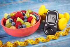 Fresh fruit salad, glucometer, centimeter and dumbbells, diabetes, healthy lifestyle and nutrition concept. Fresh fruit salad, glucose meter with result of sugar Royalty Free Stock Photography