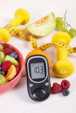 Fruit salad, glucose meter, centimeter and dumbbells, diabetes, healthy lifestyle and nutrition concept. Fresh fruit salad, glucose meter with result of sugar Royalty Free Stock Photos