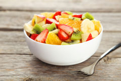 Fresh fruit salad on grey wooden background. Royalty Free Stock Images