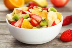 Fresh fruit salad on grey wooden background. Fresh fruit salad on grey wooden background Royalty Free Stock Photo