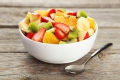 Fresh fruit salad on the grey wooden background. Fresh fruit salad on grey wooden background Royalty Free Stock Image