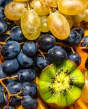 Fresh fruit salad made of banana, kiwi, and grapes pieces royalty free stock photos