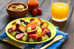 Fresh Fruit Salad. Made of grape, strawberry, plum and nectarine served on plate with walnut, nectarine, strawberry, juice in the back, photographed on dark Stock Photos