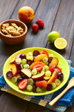 Fresh Fruit Salad. Made of grape, strawberry, plum and nectarine served on plate with walnuts, lemon in the back, photographed on dark wood with natural light ( Stock Photo