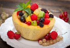 Fresh fruit salad in the melon Stock Images