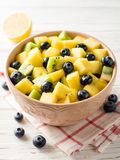Fresh fruit salad with pineapple, mango, kiwi and blueberries on white wooden background. Selective focus Royalty Free Stock Images