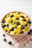 Fresh fruit salad with pineapple, mango, kiwi and blueberries on white wooden background. Selective focus Stock Images