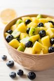 Fresh fruit salad with pineapple, mango, kiwi and blueberries on white wooden background. Selective focus Royalty Free Stock Photography