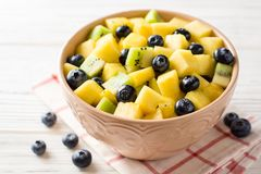 Fresh fruit salad with pineapple, mango, kiwi and blueberries on white wooden background. Selective focus Stock Image