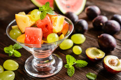 Fresh fruit salad with watermelon, plums, nectarines and grape. Fresh juicy fruit salad with watermelon, plums, nectarines and grape in a glass jar on a wooden Stock Photos
