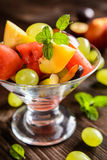 Fresh fruit salad with watermelon, plums, nectarines and grape. Fresh juicy fruit salad with watermelon, plums, nectarines and grape in a glass jar on a wooden Royalty Free Stock Image