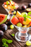 Fresh fruit salad with watermelon, plums, nectarines and grape. Fresh juicy fruit salad with watermelon, plums, nectarines and grape in a glass jar on a wooden Royalty Free Stock Photos
