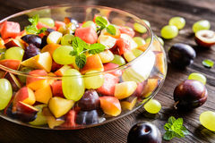 Fresh fruit salad with watermelon, plums, nectarines and grape. Fresh juicy fruit salad with watermelon, plums, nectarines and grape in a glass jar on a wooden Stock Photography
