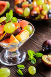 Fresh fruit salad with watermelon, plums, nectarines and grape. Fresh juicy fruit salad with watermelon, plums, nectarines and grape in a glass jar on a wooden Stock Images