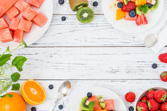 Fresh fruit salad on wooden table. Top view. Healthy fresh fruit salad on white plate on wooden table. Top view, copy space. Delicious summer meal: strawberries royalty free stock photography