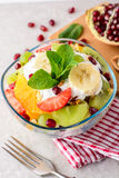 Fresh fruit salad with yogurt and walnuts in glass bowl on stone background. Royalty Free Stock Image