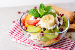 Fresh fruit salad with yogurt and walnuts in glass bowl on stone background. Stock Photo