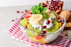 Fresh fruit salad with yogurt and walnuts in glass bowl on stone background. Stock Photography