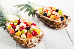 Fresh Fruit Salads in Pineapples on White Table. Close up Two Sets of Fresh Fruit Salads in Pineapple Boats For Summer Season on Top of a White Wooden Table Royalty Free Stock Photography