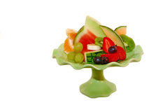 Fresh fruit selection on plate with isolated background. Fresh , sliced fruit selection on green designer plate with whiteisolated background royalty free stock images