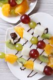 Fresh fruit on skewers with chocolate sauce vertical top view. Fresh fruit on skewers with chocolate sauce closeup. vertical top view Stock Photo