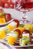 Fresh fruit on skewers and red wine close-up vertical Royalty Free Stock Images