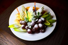 Fruits sliced on a white plate royalty free stock image