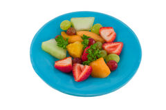 Fresh Fruit Slices. Fruit salad on a plate with strawberries, melon, grapes and pineapple Stock Photo