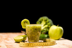 Fresh fruit smoothie in glass with piece of kiwi. Limes and measuring tape on tabletop Stock Photos