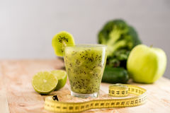 Fresh fruit smoothie in glass with piece of kiwi. Limes and measuring tape on tabletop Royalty Free Stock Image