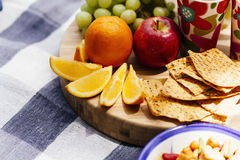 Fresh fruit and snacks on picnic blanket Royalty Free Stock Image