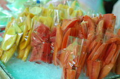 Fresh fruit sold at a market. Fresh fruit cut and sold in pieces ready to be eaten at a market in thailand Stock Photos