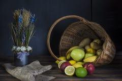 Fresh fruit spilling out of basket. Dark still life concept stock photo
