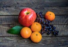 Fresh fruit, still life. Apple, tangerines, grapes Stock Photography
