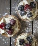 Fresh fruit tartlets on rustic wooden kitchen background Stock Images