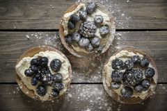 Fresh fruit tartlets on rustic wooden kitchen background Stock Photography
