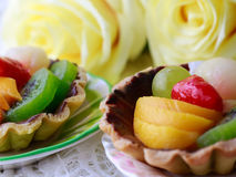 Fresh fruit tarts on white panel include kiwi, lychee,grapefruit, strawburry,peaches on top Stock Images