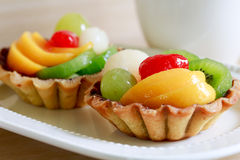 Fresh fruit tarts on wooden panel and a herbal tea. Fresh fruit tarts on wooden panel include kiwi, lychee,grapefruit, strawburry,peaches and a cup of herbal tea Stock Photography