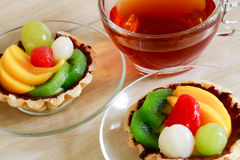 Fresh fruit tarts on wooden panel and a herbal tea Royalty Free Stock Photos