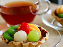 Fresh fruit tarts on wooden panel. Include kiwi, lychee,grapefruit, strawburry,peaches and a cup of herbal tea on wooden table Royalty Free Stock Photos