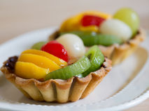 Fresh fruit tarts on wooden panel Stock Images