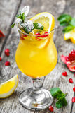Fresh fruit tropic cocktail with mint, lemon and pomegranate in glass on wooden background. Summer drinks and alcoholic cocktails Royalty Free Stock Image