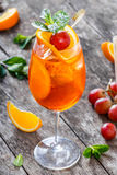 Fresh fruit tropic cocktail with mint, orange and grapes in tall glass on wooden background. Summer drinks and alcoholic cocktails Royalty Free Stock Photography
