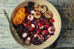Fresh fruit and vegetable salad in the plate or in bowl on woode. Bright summer salad on wooden table Royalty Free Stock Photos