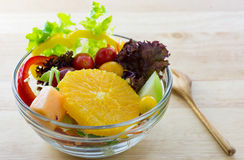 Fresh fruit and Vegetable salad on a wooden plate.  Stock Photo
