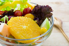 Fresh fruit and Vegetable salad on a wooden plate.  Stock Photography