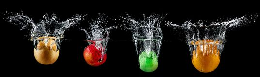 Fruit in water splash. Fresh fruit in water splash on black background stock photos