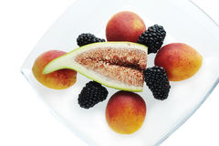 Fresh fruit on white plate. Fresh fig, apricots and blackberries on white background Royalty Free Stock Photography