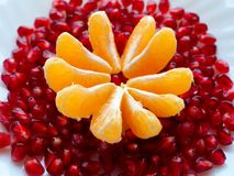 Fresh fruit on a white plate . Slices of Mandarin and pomegranate grains. royalty free stock photo