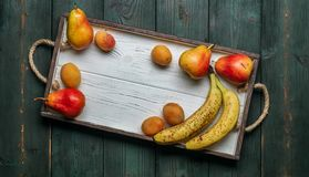 Fresh fruit on a white wooden tray: banatas, pears, apricots. Countryside setting. Top view. stock photos